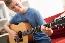 Teenage Boy Sitting On Sofa At Home Playing Guitar