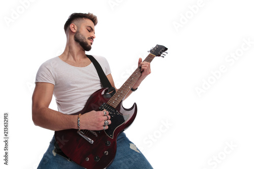 young man performing a rock and roll concert on guitar Fototapeta