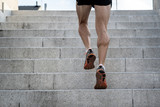 Fototapeta Na drzwi - Close up of young man running up the stairs with running clothes