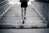 Fototapeta Na drzwi - black and white closeup of young man running up the stairs with running clothes