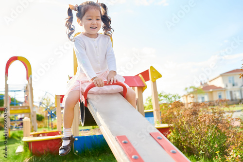 Portrait of cute little Asian girl having fun playing on playground outdoors on swings