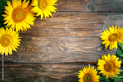 Foto op Aluminium Zonnebloem Beautiful sunflowers on a wooden table. View from above. Background with copy space.