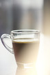 Black espresso coffee with heady froth in a glass mug or cup, light toning