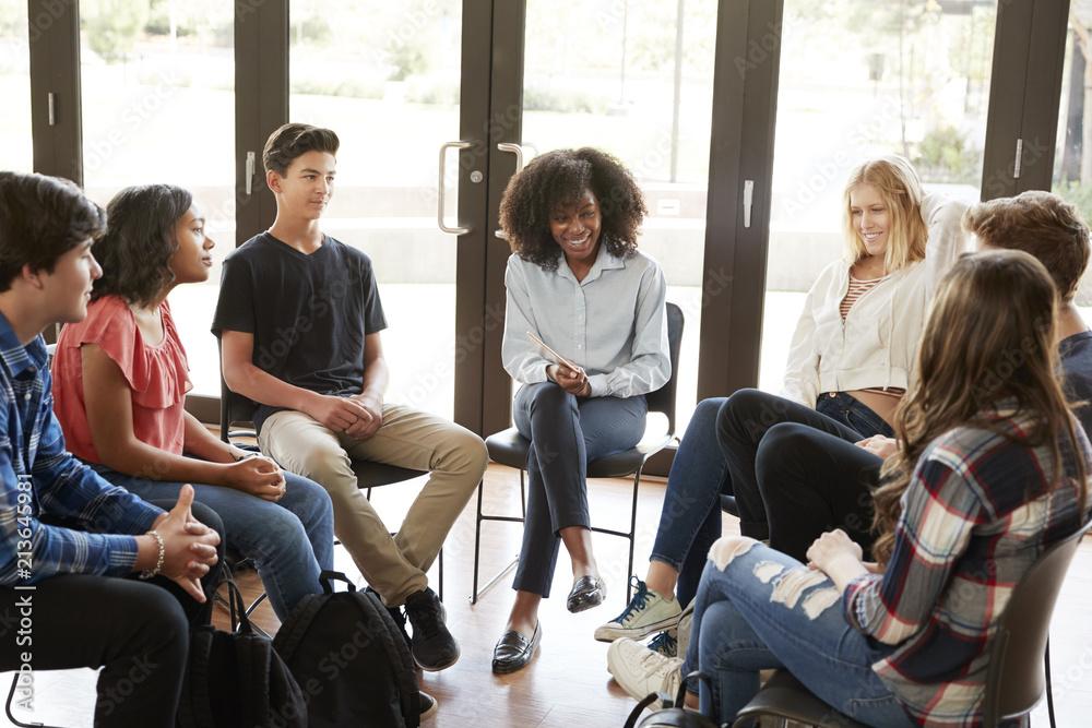 Fototapeta Female Tutor Leading Discussion Group Amongst High School Pupils