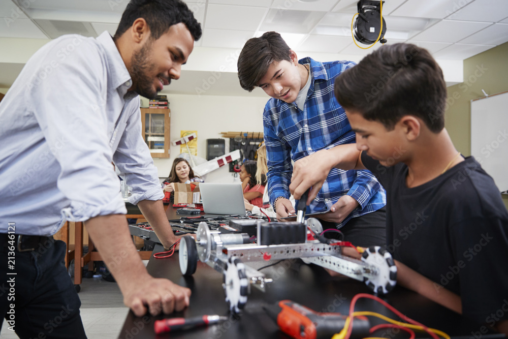 Fototapeta Teacher With Male Pupils Building Robotic Vehicle In Science Lesson