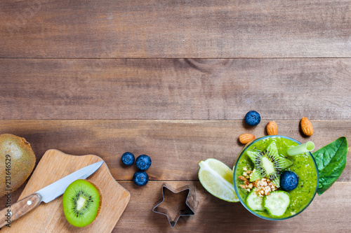 Fotografía Wooden background with glass of green healthy smoothie