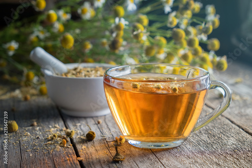 Healthy chamomile tea or infusion, mortar and daisy herbs on wooden board.