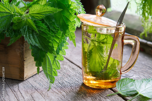 Healthy nettle tea or infusion and nettle herbs on wooden table in retro village house.