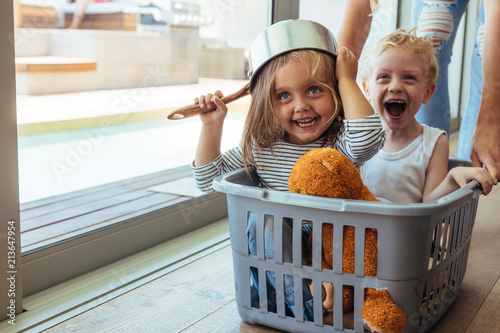 Fototapeta Kids rides in a laundry basket obraz