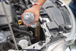 Hand pouring water for radiator in car engine. Self checking radiator water for windscreen