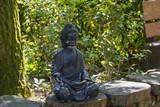 horizontal image of a black stone statue depicting Buddha