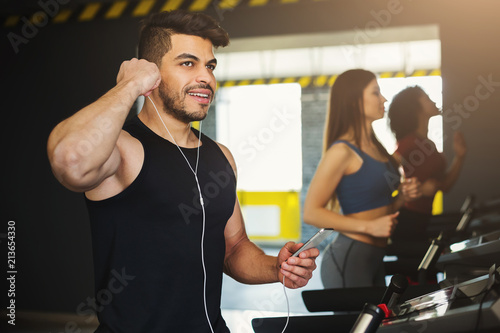 Keuken foto achterwand Ontspanning Handsome guy listening music while training on treadmill