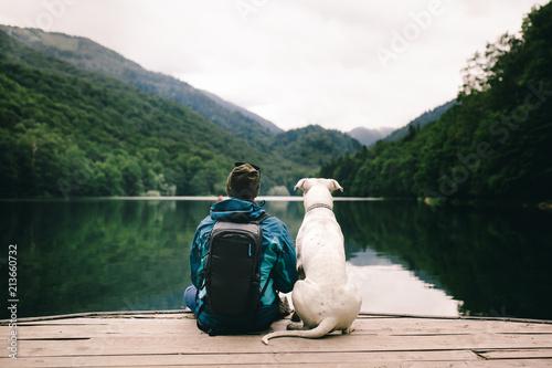 Slika na platnu Man sitting with a dog on dock at the lake