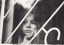 Black And White Portrait Of Sad Little Girl Looks Through Window With Lattice