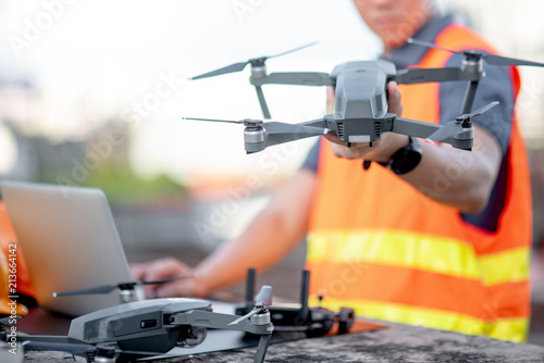 Young Asian engineer man working with drone laptop and smartphone at construction site Fototapete