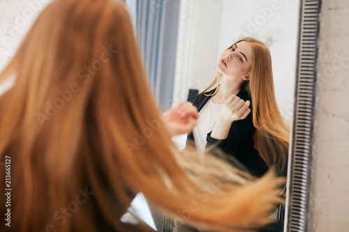 Girl taking care of her hair on hairdresser shop