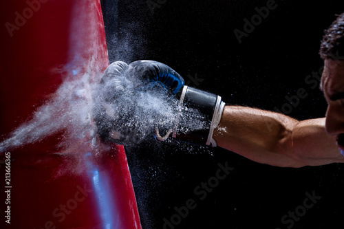 Close-up hand of boxer at the moment of impact on punching bag over black backgr Canvas Print