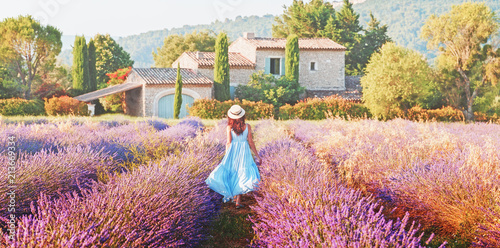 Ingelijste posters Nice Lovely girl dressing in blue boho chic dress and straw hat walking amazing blooming field of lavender in Provence, France. Panoramic view. Post production photo in traditional Provencal pastel tones.
