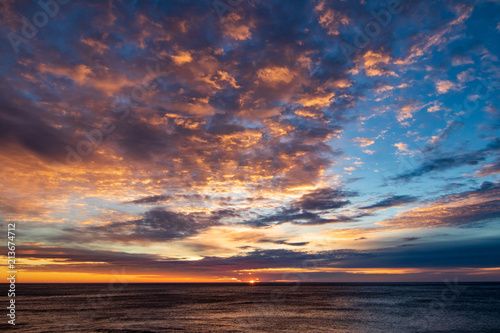Spoed Foto op Canvas Zee zonsondergang Dramatic sunrise clouds. Very structured and colorful sky. Blue, orange, pink, yellow. Sun rising on horizon about sea. Adventure, clean, sail, free, quiet, relax, holiday.