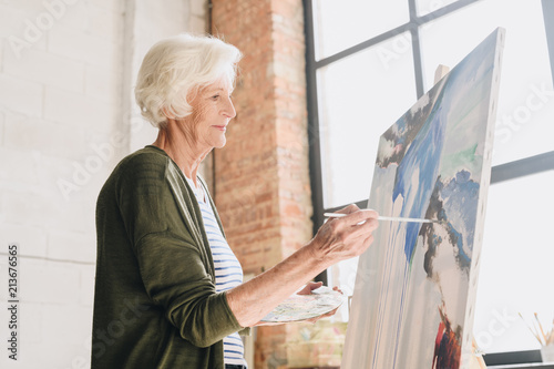 Side view portrait of white haired senior woman holding palette painting pictures at easel in  art studio standing against windows in sunlight, copy space