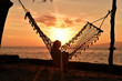 Siilhouette of woman sitting in hammock at sunrise on the beach, Gili Meno Island, Lombok, Indonesia