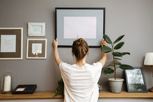 Girl Hanging A Frame On A Gray Wall
