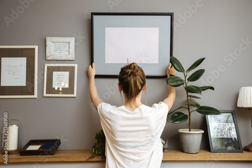 Mur Girl hanging a frame on a gray wall