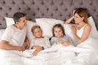 Couple with children lying under blanket in bed. Happy family