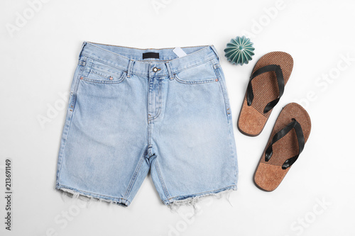 Obraz Flat lay composition with jean shorts and slippers on white background - fototapety do salonu