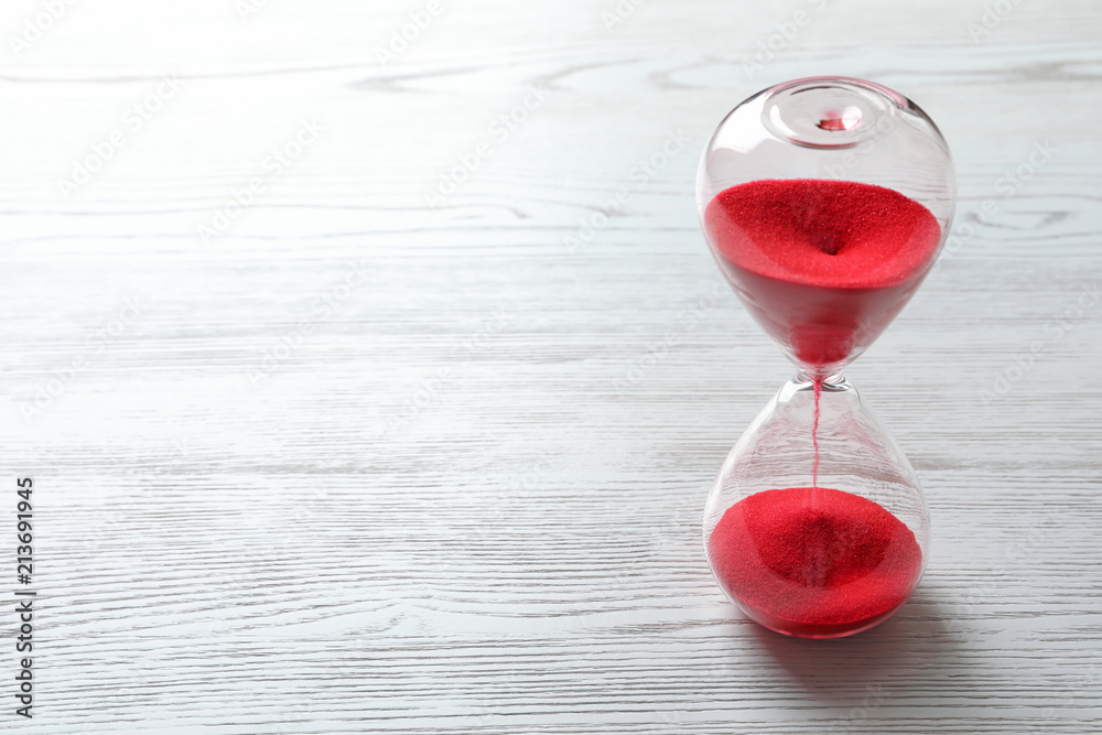 Fototapeta Hourglass with flowing red sand on wooden background. Time management