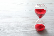 Hourglass With Flowing Red Sand On Wooden Background. Time Management