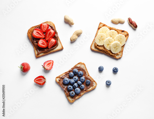 Fényképezés Tasty toast bread with banana, strawberry and blueberry on white background
