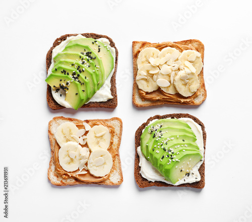 Cuadros en Lienzo Tasty toast bread with banana and avocado slices on white background