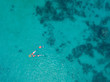 Beautiful sea view, shot by drones. People swim in the transparent sea between coral reefs. Aerial view of tourists swimming in beautiful clear sea water.
