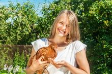 Girl Feeding Brown Chicken