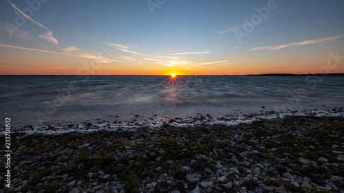 Keuken foto achterwand Grijze traf. dramatic sunrise over the baltic sea with rocky beach and trees on the shore