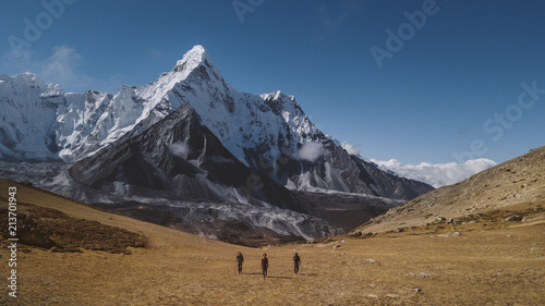 Hikers walking on landscape against blue sky