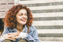 Close-up Of Happy Woman Looking Away While Sitting Against Wall