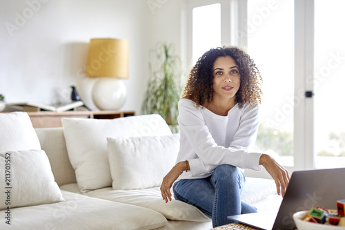 Portrait of woman with laptop computer sitting on sofa at home
