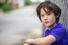 Portrait Of Boy Sitting On Street By Fence