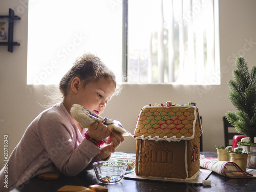 Side view of girl icing on gingerbread house while sitting at home†