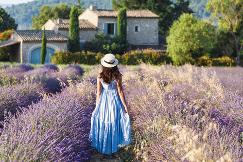 Beautiful view on Lavender fields in Provence, France. National park Luberon, Sault village. Lovely young Caucasian woman enjoying the blooming lavender fields walking.