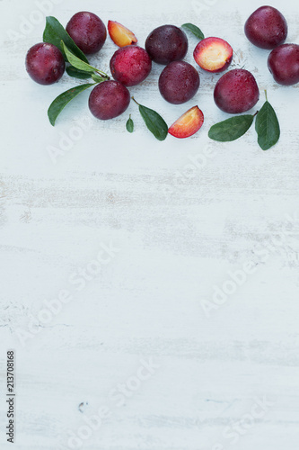 Fresh plums with leaves on white rustic wooden table background.