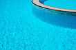 Background of water surface in blue swimming pool with the edge