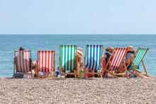 Rear View Of Group Of People Seated In Six Striped Deckchairs At The Seaside On A Bright Sunny Summer Day