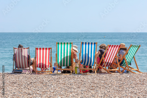 Canvas Print Rear View of Group of People Seated in Six Striped Deckchairs at the Seaside on