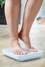 Woman Standing On Weight Scale...