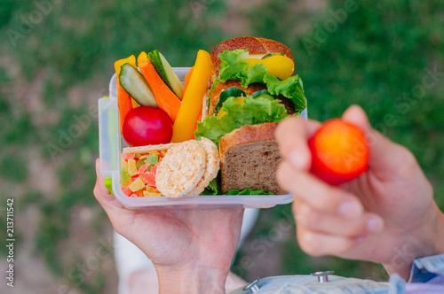 Foto op Aluminium Assortiment Close up of young woman eating from lunch box outdoor