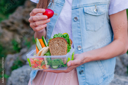 In de dag Assortiment Closeup of woman eating from lunch box outdoor