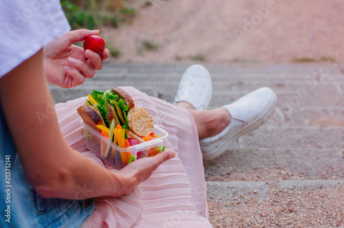 Foto op Aluminium Assortiment Young hipster girl eating from lunch box sitting in the stairs outdoor